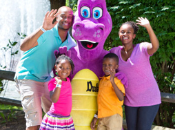 Family of 4 standing and waving with Duke the Dragon