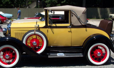 A antique yellow car sits within the park at Idlewild