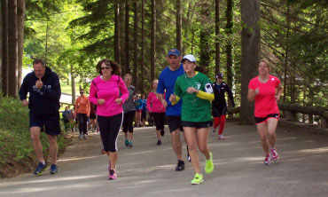 Runners through Idlewild park on a tree lined hill