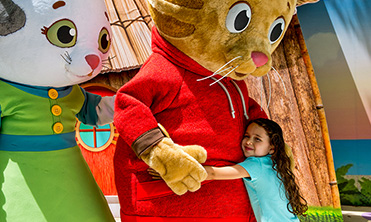 Young girl hugging Daniel Tiger character