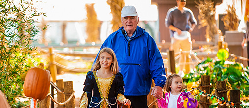 Grandfather walking with costumed granddaughters