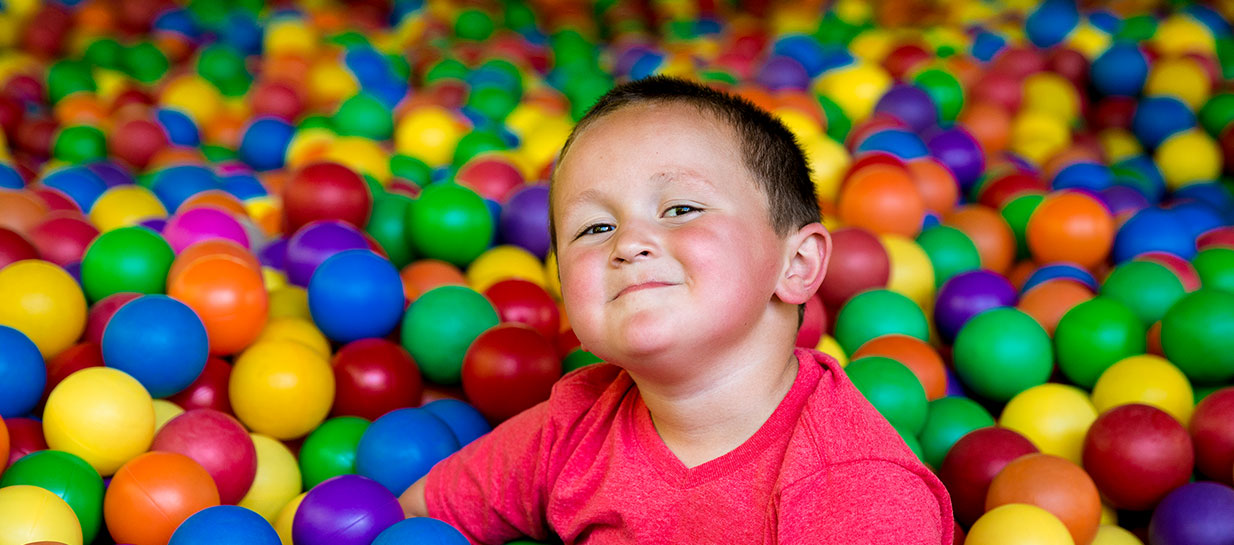 Smiling boy in plastic ball pit