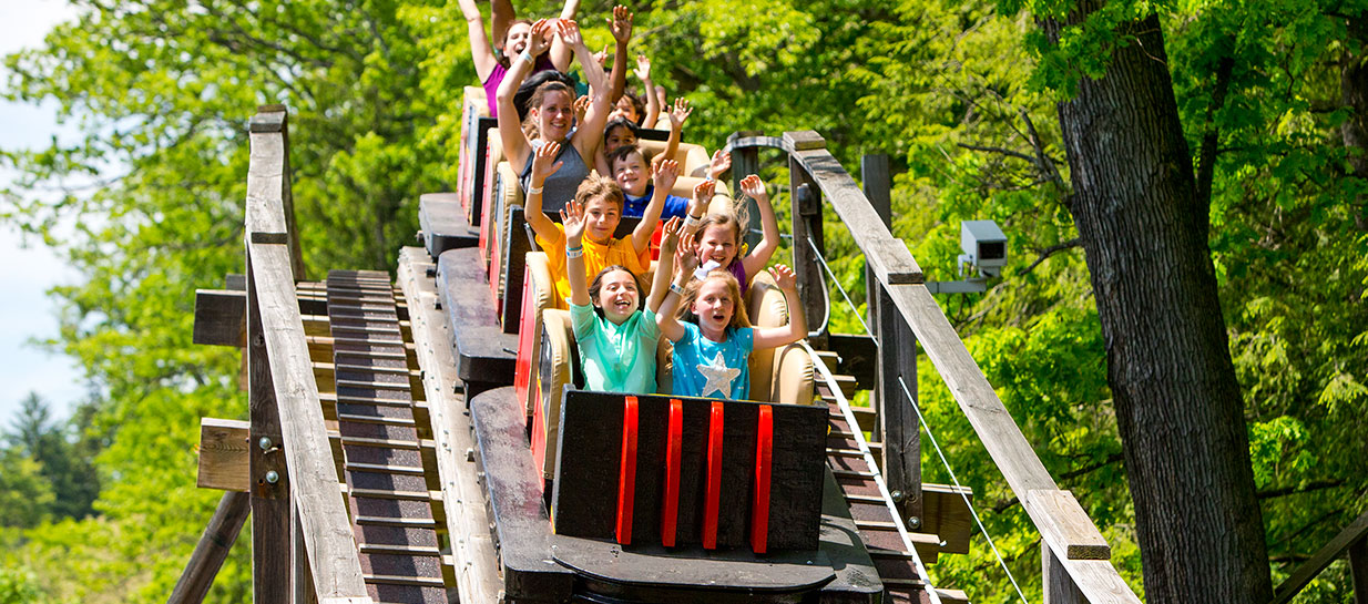 Coaster riders with arms up going downhill