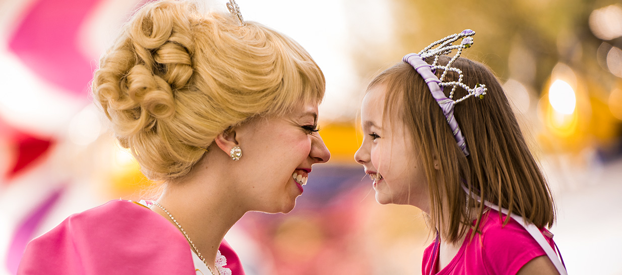 Princess and young girl imitating one another