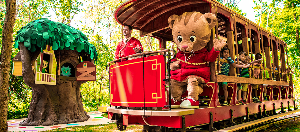 Daniel Tiger riding trolley with children through magical park