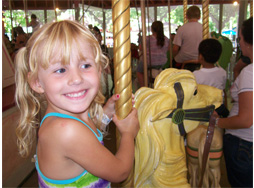 Little girl on Carousel Horse with big smile
