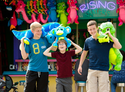 3 Boys carrying plush animals from Idlewild games
