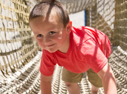 Boy climbing the rope tunnel